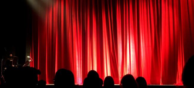 червена завеса в театър и зрители на седалките
