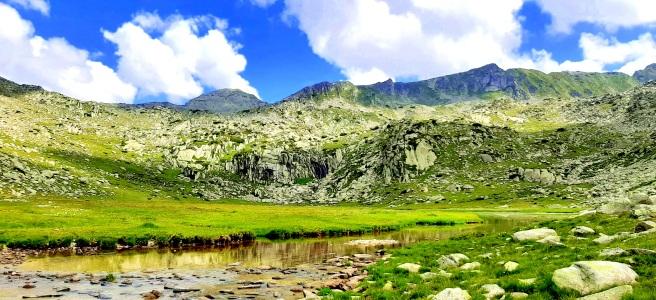 Голямото Спанополско езеро в планина пирин, в местността Спанополско поле, около нега се виждат зелена поляна и планински върхове и хълмове
