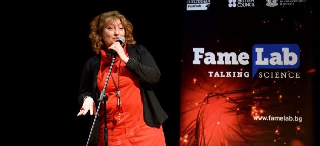 Любов Костова говори на сцената на FameLab. Облечена е в червена роклю и носи черна жилетка.