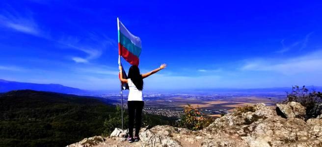 момиче в бяло и черно на връх половрак в лозенската планина, хванало българското знаме